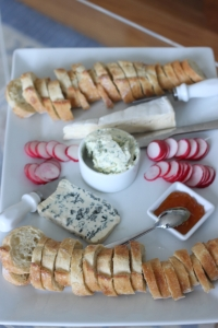 Herbed butter (center), sliced radishes and sliced baguettes along with some cheeses