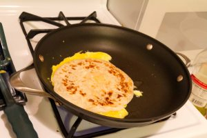Put the cooked paratha on the egg as it cooks