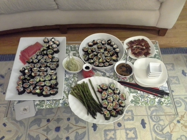 Sushi for 4: tuna, spicy tuna, eel, salmon, cream cheese and veggies all in various rolls, tuna and eel on the side, served with wasabi, eel sauce and roasted asparagus